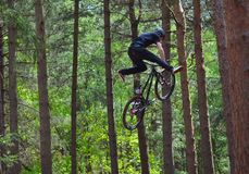 Freestyle  Stunt Cyclist in mid air very high with trees in background. HAYNES, BEDFORDSHIRE, ENGLAND - MAY 14, 2017:  Freestyle  Stunt Cyclist in mid air very Stock Photo