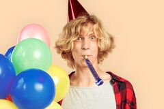 Freestyle. Teen blond boy in birthday cap standing isolated on nude color with balloons blowing party horn smiling