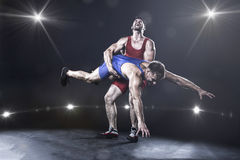 Freestyle wrestler throwing. Wrestler throwing against the lights on background royalty free stock photography
