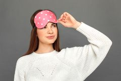 Freestyle. Young girl in sleeping mask standing isolated on grey smiling playful close-up stock images