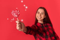 Freestyle. Young girl standing isolated on red with heart shaped lollipop close-up smiling happy blurred stock images