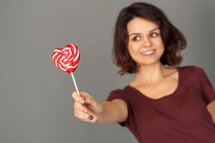 Freestyle. Young woman isolated on grey with lollipop close-up smiling excited blurred stock image