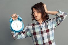 Freestyle. Young woman isolated on grey looking at alarm clock touching head shocked close-up royalty free stock images