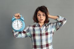 Freestyle. Young woman isolated on grey showing alarm clock touching head mouth opened concerned royalty free stock photography