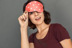 Freestyle. Young woman in sleeping mask on grey looking camera excited close-up stock photography