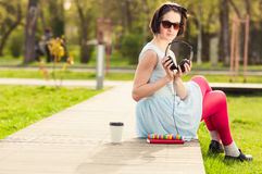 Freetime concept with female relaxing outdoors with music and co. Freetime concept with beautiful female relaxing outdoors with music, books  and coffee Royalty Free Stock Images