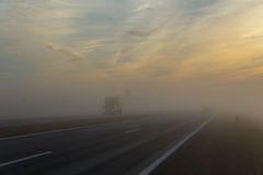 Freeway and a car in fog Stock Photos