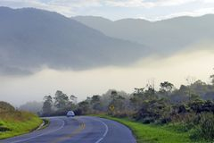 Freeway in morning fog, with car. Hills and trees. Rio Santos Road, Sao Paulo, Brazil stock images