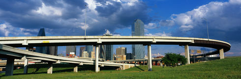 This is a freeway overpass with the Dallas skyline visible behind it. The freeway curves and snakes around in a circle in front of Royalty Free Stock Photography