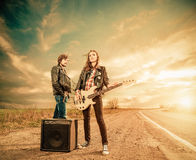 Freeway rocks. Young cute couple at windy freeway roadside with guitar stock photography