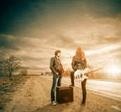 Freeway rocks. Young cute couple at windy freeway roadside with guitar stock photo