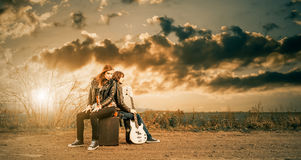 Freeway rocks. Young cute couple at windy freeway roadside with guitar royalty free stock photo