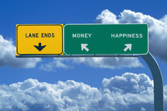 Freeway sign Money/Happiness. Freeway sign in blue cloudy skies reading Money and Happiness Royalty Free Stock Image