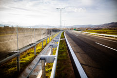 Freeway on a sunny day trough scenic green meadows.Motorway traveling long distance.Asphalt highways road Royalty Free Stock Photos
