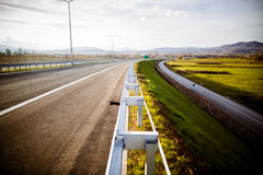 Freeway on a sunny day trough scenic green meadows.Motorway traveling long distance.Asphalt highways road in rural scene use land Stock Photo