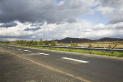 Freeway under cloudy sky Stock Images