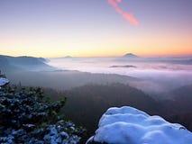 Freeze autumnal daybreak, rocks covered with fresh powder snow. Stony rock Royalty Free Stock Photography