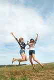 Freeze frame photography captures happy jumping of two friends Royalty Free Stock Photo