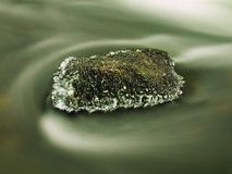 Freeze mossy sandstone boulder in dark cold water Royalty Free Stock Photography