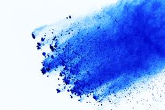 Freeze motion of blue powder explosions isolated on white background. Abstract blue powder splashed on white background. stock photo