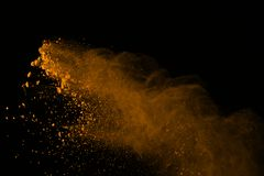 Freeze motion of gold powder explosions isolated on black background. colored dust explosive on dark background. Colorful cloud s stock photos