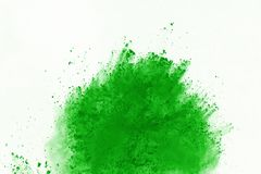 Colored powder explosion. Colore dust splatted. Freeze motion of Green powder exploding on white background royalty free stock photos