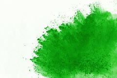 Colored powder explosion. Colore dust splatted. Freeze motion of Green powder exploding on white background royalty free stock images