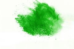 Colored powder explosion. Colore dust splatted. Freeze motion of Green powder exploding on white background stock photos