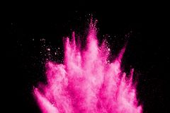 Freeze motion of pink powder exploding. Abstract pink dust splattered on dark background, Freeze motion of pink powder exploding royalty free stock image