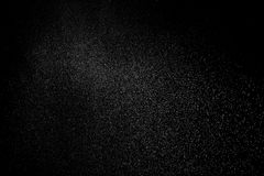 Freeze motion of white particles on black background. White granule explosion. Abstract white dust overlay texture Royalty Free Stock Photos
