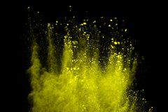 Freeze motion of yellow dust explosion isolated on black background. royalty free stock photos