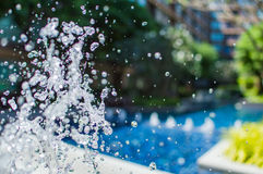 Freeze splashing droplets of water in the air near the swimming pool. Close up image Royalty Free Stock Photography