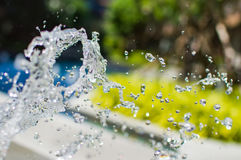 Freeze splashing droplets of water in the air near the swimming pool. Close up image Royalty Free Stock Images