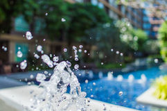 Freeze splashing droplets of water in the air near the swimming pool. Close up image Stock Photos