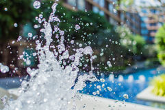 Freeze splashing droplets of water in the air near the swimming pool. Close up image Royalty Free Stock Image