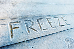 Freeze written on a wooden background with frosts Stock Image