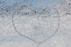 Freezed hjärta på fönstret Arkivbild