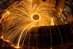Freezelight using spinning burning steel wool and pyrotechnics in abandoned fact Royalty Free Stock Image