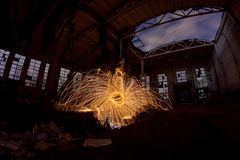 Freezelight using spinning burning steel wool and pyrotechnics in abandoned fact Royalty Free Stock Photo