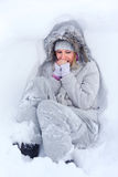 Freezing. Beautiful young woman in white winter clothes lying in the snow and freezing. Warms your breath their own hands Stock Photos