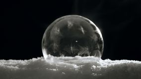 Freezing bubble Ice ball for Christmas and New Year. Fast Freezing Soap bubble. Ice ball with flying snowflakes on snow and black background in cold winter. For stock footage
