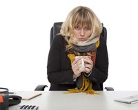 Freezing businesswoman warming up with coffee Royalty Free Stock Photography