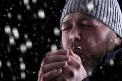Freezing cold man in snow storm. Freezing cold man standing in a snow storm blizzard trying to keep warm. Eyes closed and blowing warm air into his hands Stock Photo
