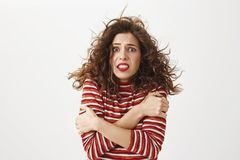 It is freezing cold outside. Indoor shot of poor attractive girl with curly hair that flows on wind, hugging herself and. Trembling, standing without coat on Stock Photos