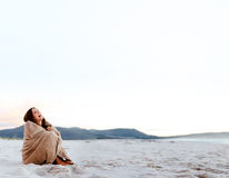 Freezing cold woman. Cold woman wraps blanket over hersolf while sitting on the beach after sunset. copyspace provided by panoramic image royalty free stock photo