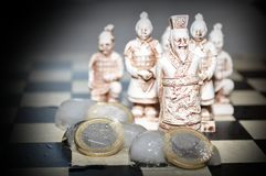 Freezing Euro coins vs chinese army Stock Photos