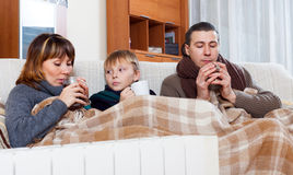 Freezing family of three   warming near warm radiator. Freezing family of three with cups of tea warming near warm radiator in home Royalty Free Stock Photography