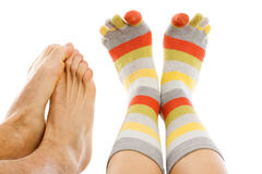 Freezing foot. Freezing naked feet of a man and a woman 's feet with warm socks isolated on white - abstract illustration of cold, of freezing Royalty Free Stock Photos