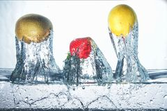 Freezing fruit in cold water. Splashing fruits views the other side Royalty Free Stock Photos