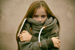 Freezing girl snuggles in her woolen sweater. Freezing girl with wonderful long brown hair snuggles in her new woolen sweater, retro look Royalty Free Stock Photos